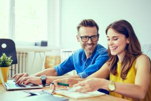 Couple devant son ordinateur en train de faire des calculs et des papiers
